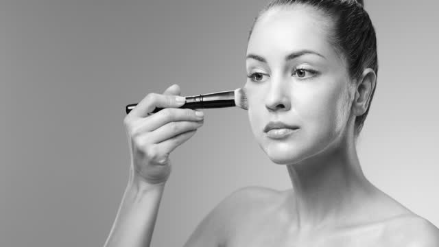 Steps of make-up applying. Girl applies foundation on the cheekbones with a make-up brush. Black and white video. video