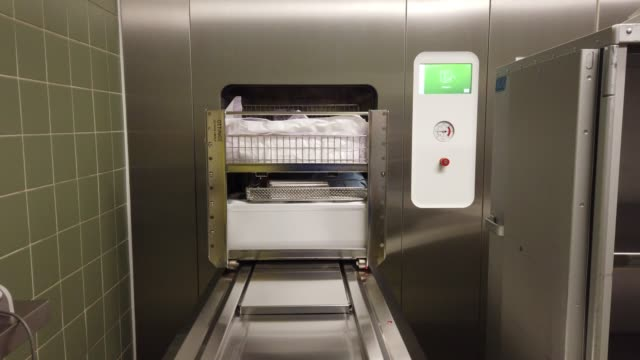 gli strumenti sterili vengono scaricati automaticamente da uno sterilizzatore a vapore - autoclave video stock e b–roll