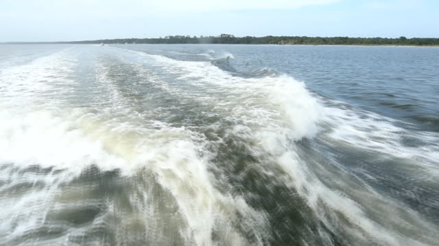 Stern view of prop wash with island on horizon video