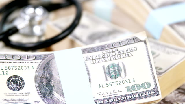 Stethoscope laying on stacks of hundred dollar currency video