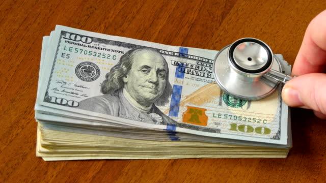 stethoskop auf geld dollar cash währung banknote - medizinexamen stock-videos und b-roll-filmmaterial