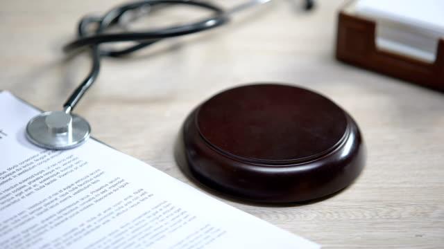 Stethoscope on table, gavel striking on sound block, injury compensation, crime