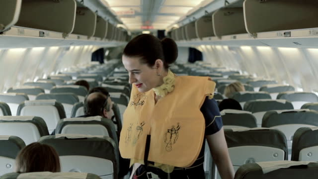 Stewardess in life vest checks the safety of passengers at the airplane video