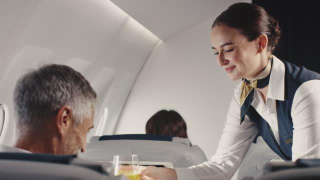 vídeos y material grabado en eventos de stock de stewardess ofreciendo almuerzo a un hombre de negocios en jet - viaje en primera clase