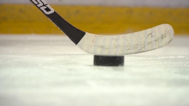 vidéos et rushes de bâton frapper la rondelle de hockey frappé au ralenti - hockey sur glace