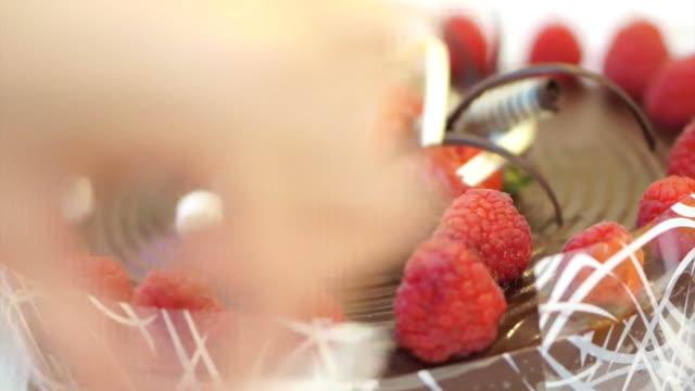ciambellina torta al cioccolato con fragole e frutti di bosco freschi - theobroma video stock e b–roll