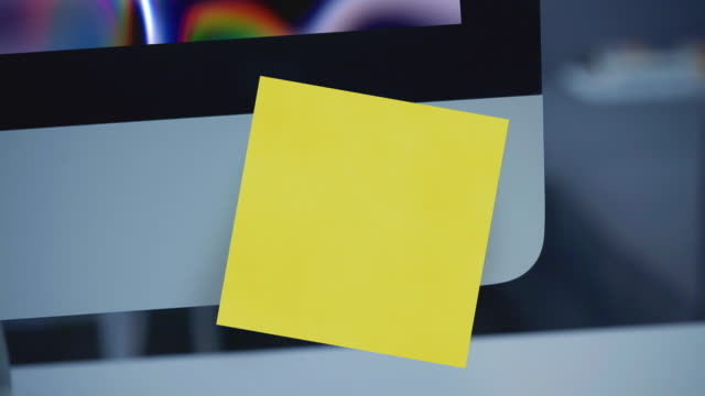 sticky notes. paper sticker on the monitor. reminder. space for text. list of important cases. - promemoria video stock e b–roll