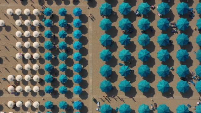 Still Aerial Footage Of White Beach Umbrellas On The Left And Blue Beach Umbrellas On the Right While People Walk Around