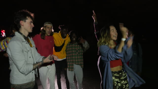 Still in Party Mode Small group of young friends are singing and dancing as they leave a music concert. party stock videos & royalty-free footage