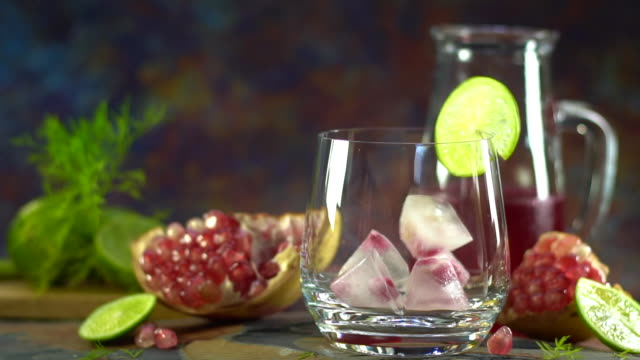 stillleben fotografie von granatapfelsaft zitronensoda mit granatapfelsamen auf dem tisch. aufnahme im studio, niedrige taste getöntes bild, selektiver fokus und freier platz für text. gesundes obstgetränk - tropischer cocktail stock-videos und b-roll-filmmaterial