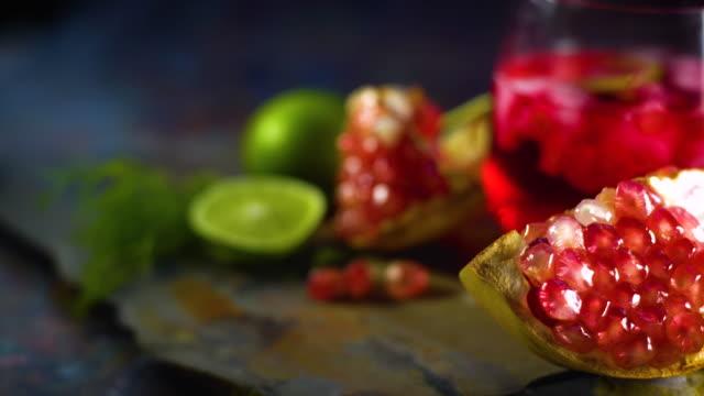stillleben fotografie von granatapfelsaft zitronensoda mit granatapfelsamen auf dem tisch. aufnahme im studio, niedrige taste getöntes bild, selektiver fokus und freier platz für text. - tropischer cocktail stock-videos und b-roll-filmmaterial