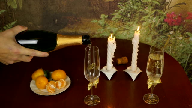 Still life with wine and a snack on the table. The hand pours the champagne over the glasses. Rings are the symbol of the bride and groom. Mandarins are on the table.