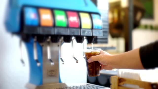 MS Still Shot and Defocused with drink dispenser corner of self service in restaurant, man's hand presses the soft drink dispenser.