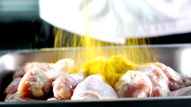 stockvideo's en b-roll-footage met ecu nog shot: gieten curry poeder aan rauwe kip benen voor het koken. - {{asset.href}}