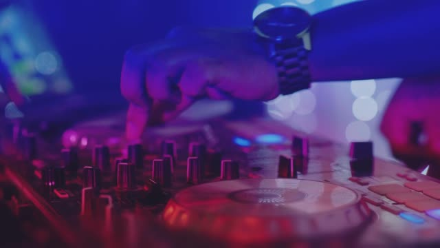 A still unused DJ mixer under glowing lights. Hands of DJ tweak controls on record deck in nightclub performer stock videos & royalty-free footage