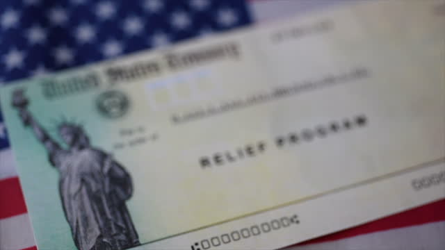 Stimulus relief program check (Economic Impact Payment) getting blur on American flag background. Close up view. Stimulus relief program check (Economic Impact Payment) getting blur on American flag background. Close up view. stimulus stock videos & royalty-free footage