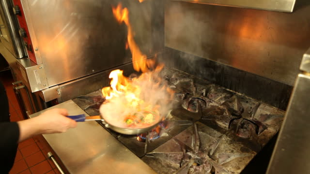 Stir Fry Cooking in Flaming Pan Wet vegetables added to a pan of hot oil for a flambe stir fry. The water creates an intense flash of flame. This could also be used for a cooking danger concept, what happens when water is added to hot oil.