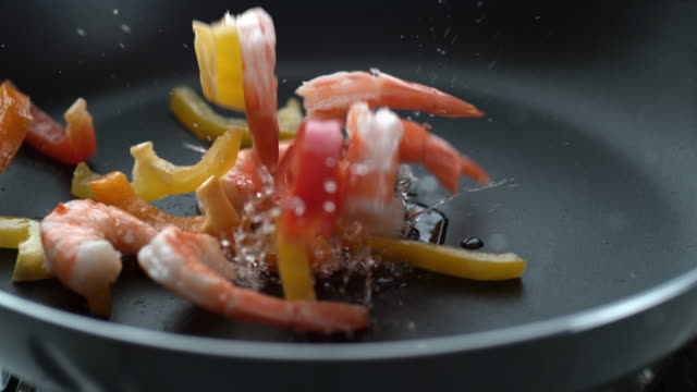 Stir fry splashing into hot oil in frying pan, slow motion video