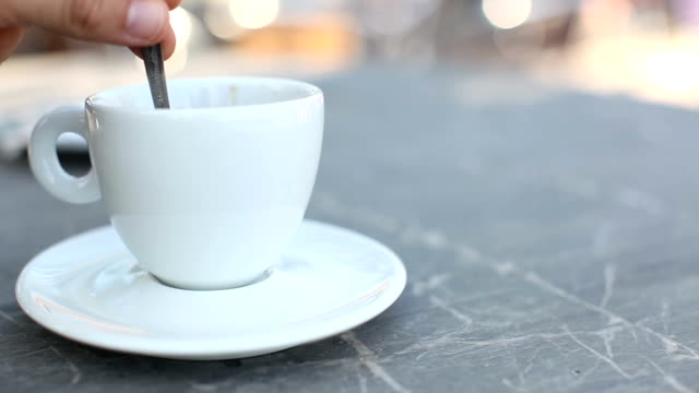 Stirring a cup of fresh coffee on a marble cafe table, outdoors Stirring a cup of fresh coffee on a cafe table, outdoors coffee cup stock videos & royalty-free footage