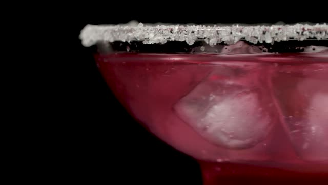 Stirring a Strawberry Cocktail on Black Background in Macro Shot. Alcoholic Drink Margarita with Ice Alcoholic cocktail in macro photography is mixed in a glass of Margarita, a rich blue color margarita stock videos & royalty-free footage