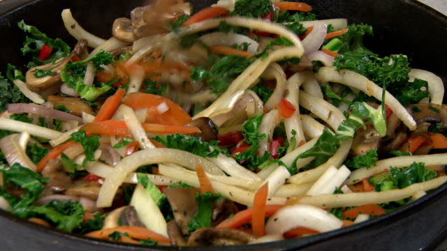 stirring and cooking veggies close-up video