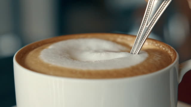 stirring cappuccino slow motion - deser filmów i materiałów b-roll