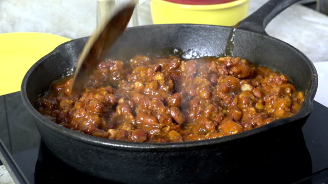 stirring chili con carne in a pan - chilli con carne video stock e b–roll