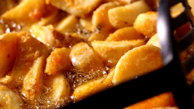 Stirring in wedges potato frying in hot boiling oil video