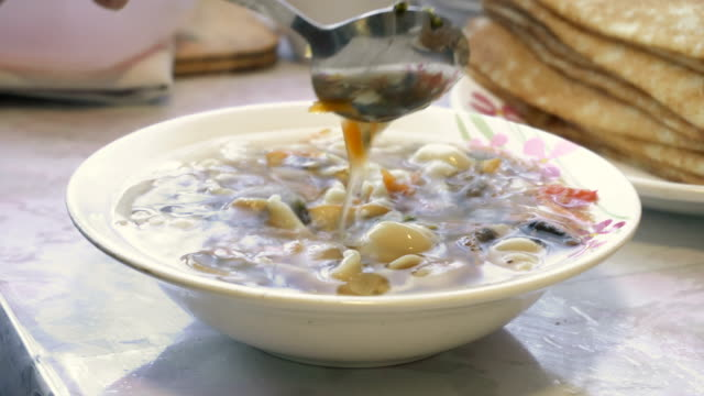 Stirring meatless soup of spoon