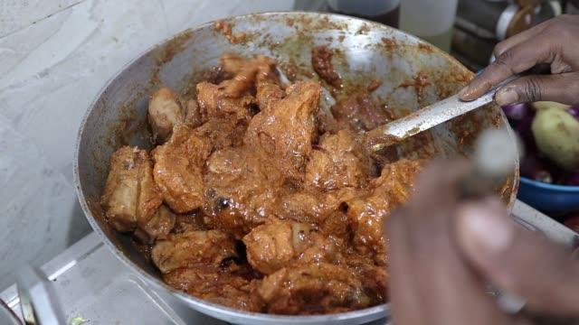 vídeos y material grabado en eventos de stock de agitación de la salsa de curry de pollo en un utensilio de sartén de acero en la llama de gas en la cocina india. - cuenco