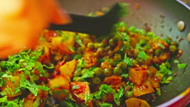 新鮮なシラントロを加えてポテトカレーをかき混ぜる - ベジタリアン料理点の映像素材/bロール