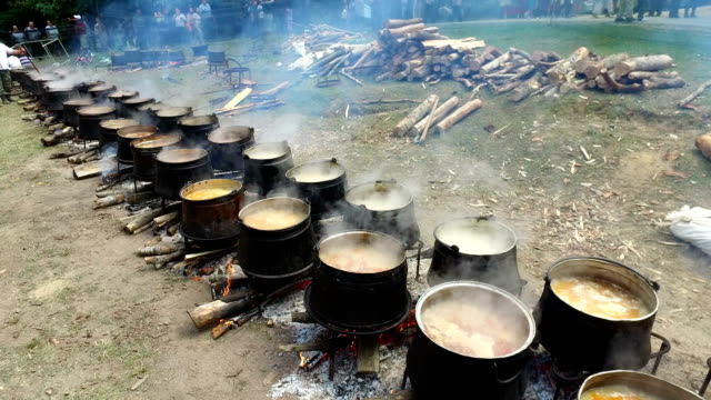 Stirring traditional meat, potatoes stewed with paprika and onions in a cauldron ( stew-pot ) on a campfire video