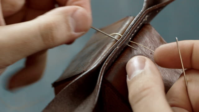 Stitching leather manually. video