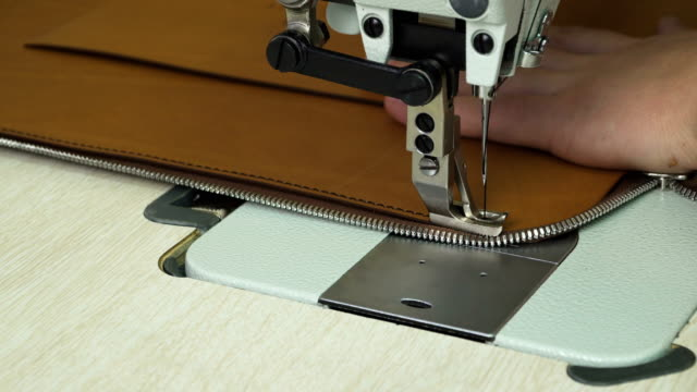 stitching leather product with modern sewing machine. video
