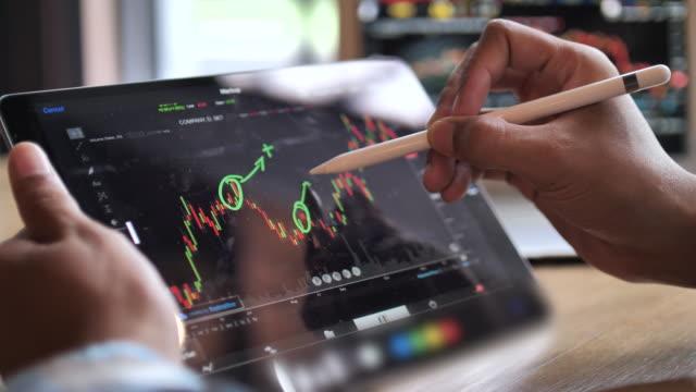 bestandsdaten analyse auf tablet pc - börsenhandel finanzberuf stock-videos und b-roll-filmmaterial