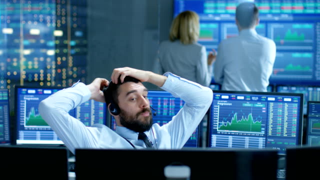 stock exchange trader makes a deal with big client over the headset. he works with other brokers and is surround by computers with graphs and ticker numbers on screens. - stock broker stock videos & royalty-free footage