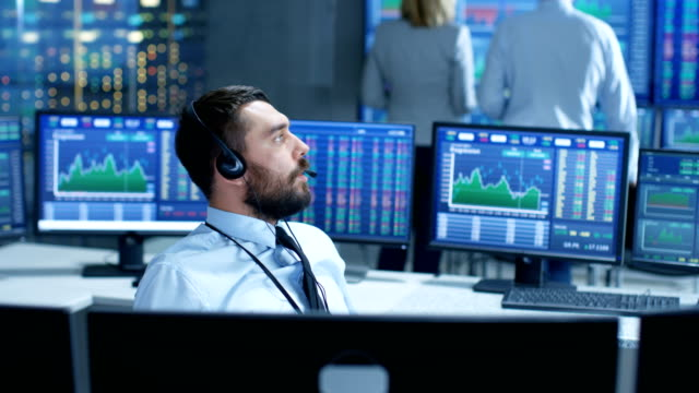 Stock Exchange Trader Makes a Deal with Big Client Over the Headset. He Works with Other Brokers and is Surround By Computers with Graphs and Ticker Numbers on Screens. video