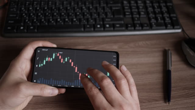 Stock Exchange, Trading Online, Trader Working With Smartphone on Stock Market Trading Floor. Man Touch Screen Reading Financial News, Browse Foreign Exchange Market Data, Chart Forex. Crypto currency
