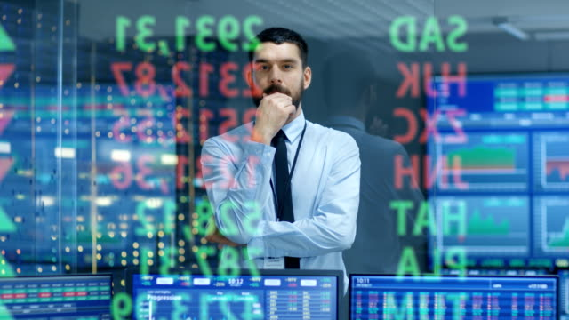 stock market top trader looks at projected ticker numbers and graphs running, analysing data to make best sell. behind him room full of screens and statistics. - stock broker stock videos & royalty-free footage