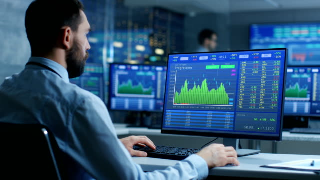 stock market trader working on a computer showing stock ticker numbers and graphs. - struttura pubblica video stock e b–roll