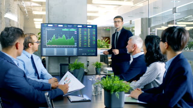 Stock Trader Gives Presentation to Executive Managers, Showing His Prognosis of the Trade Market Behavior Pointing at the Wall TV. Stock Trader Gives Presentation to Executive Managers, Showing His Prognosis of the Trade Market Behavior Pointing at the Wall TV. Shot on RED EPIC-W 8K Helium Cinema Camera. financial occupation stock videos & royalty-free footage