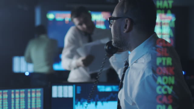 stockbroker in white shirt is talking on the phone while working in a dark monitoring room with display screens. - stock broker stock videos & royalty-free footage
