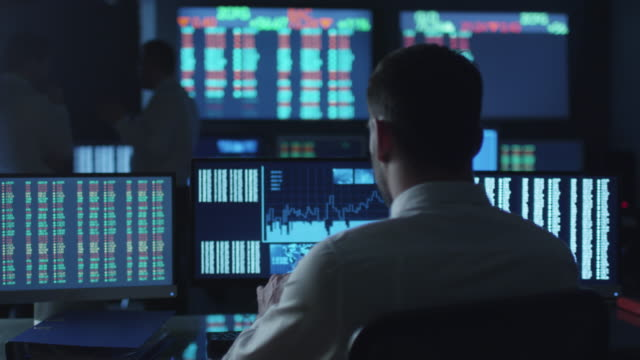 Stockbroker in white shirt is working in a dark monitoring room with display screens. video