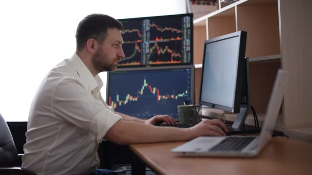 Stockbroker in white shirt is working in a monitoring room with display screens. Stock Exchange Trading Forex Finance Graphic Concept. Businessmen trading stocks online