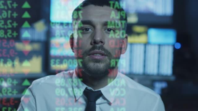 株式仲買人 はを見ているデータ、の数字は、透明ガラスの画面上でダークオフィスに表示されます。 ビデオ