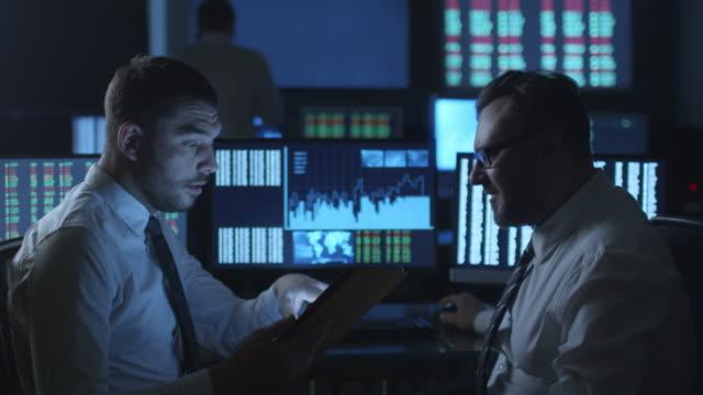 Courtier en valeurs mobilières est à l'aide d'une tablette ordinateur et avoir une conversation dans un bureau noir avec écrans d'affichage. - Vidéo