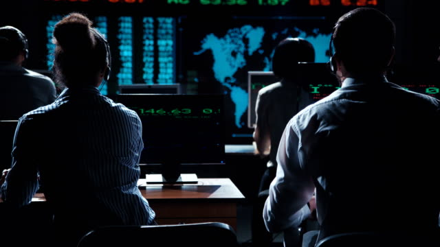 Stockbrokers watching exchange listing on screen video