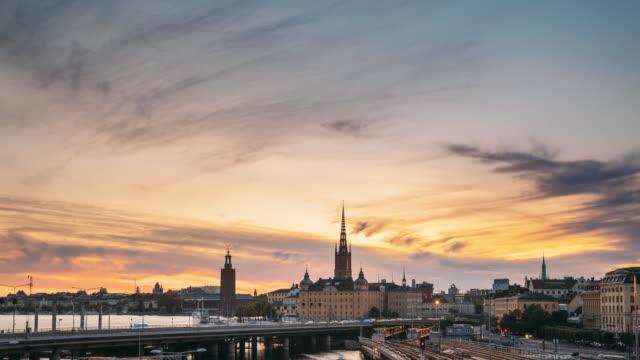 stockholm, sverige. vacker utsikt över stockholms stadssilhuett på sommarkvällen. berömd populär destination naturskön plats i solnedgången ljus. riddarholmskyrkan och tunnelbanetåg. dag till natt övergångs tid förfaller - stockholm bildbanksvideor och videomaterial från bakom kulisserna