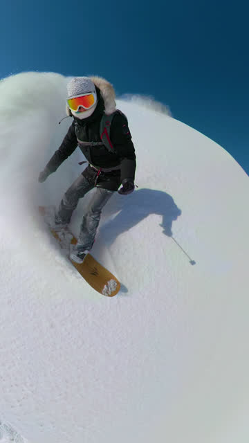 vídeos de stock e filmes b-roll de vertical: stoked snowboarder girl carving off trail high in sunny mountains. - vertical