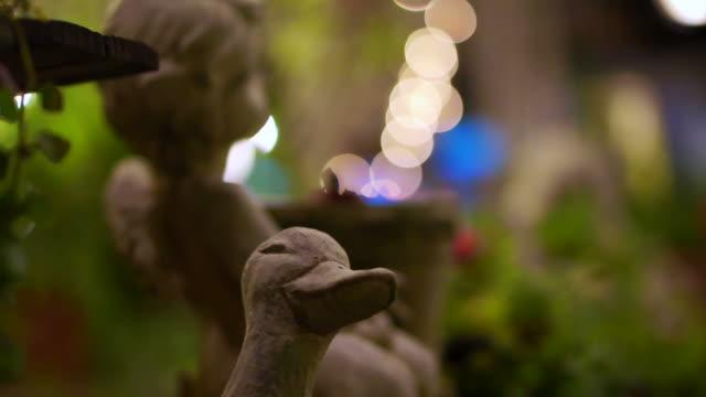 sten vinkel cupid och anka trädgård dekoration i natt trädgården. abstrakta romantisk scen - ancient white background bildbanksvideor och videomaterial från bakom kulisserna